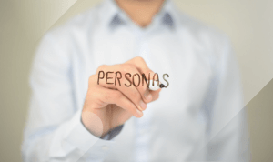 Man in a collared white shirt writing personas on a see through board representing buyer personas